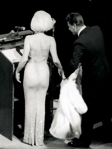 "Peter Lawford, right, tends to Marilyn Monroe's fur as she prepares to sing ""Happy Birthday"" to President John F. Kennedy at a Madison Square Garden gala in New York on May 19, 1962"