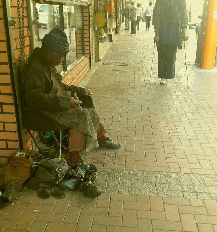 Street cobbler.  Making a living. Johannesburg city.