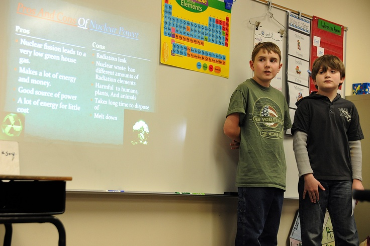 Fifth graders Logan Buzbee, 11, and Jevin Bush, 11, explain the pros and cons of nuclear power May 1 at Evans International Elementary School in Falcon School District 49. The elementary school's fifth graders, roughly 110 students, had formed 30 interest groups to explore community issues. The culminating project completes the International Baccalaureate Primary Years Program.
