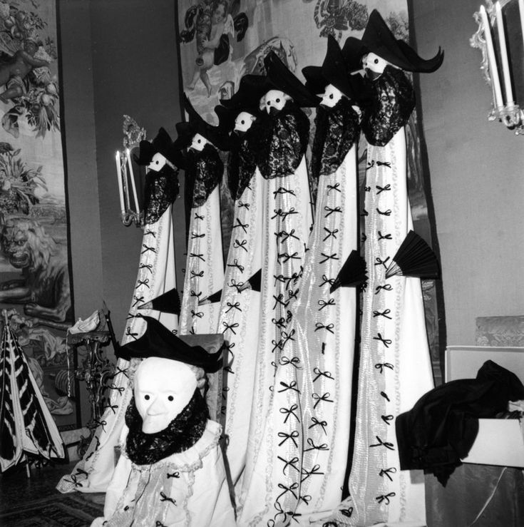 """Venice Bal Beistegui 3 September 1951 © Robert Doisneau  At the Ball of the Century, a row of bautas on one of the walls of the Palazzo Labia used as decoration for the """"Masks and Dominoes"""" evening. The bauta is a typically Venetian costume in three pieces: it includes a black three-cornered hat, a mask and a veil. It was worn in the 18th century outside the Carnival during secret meetings and often appeared in paintings by the Venetian masters of the period, such as Longhi, Guardi and…"""