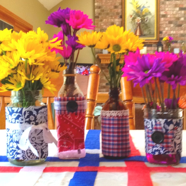 Decorate empty mason jars and bottles with red white and blue fabric, ribbons and buttons with a hot glue gun for cute flower vases!