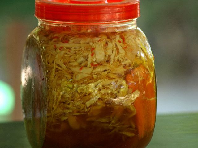 Curtido Salvadoreño - 4 c cabbage, ½ c onions, & 1 carrot, all thinly sliced; 6 c boiling water; 1 c pineapple vinegar; 1 bay leaf; 3 T salt; 1 T chicken bouillon (optional); oregano (optional). Place vegetables in a large jar and add boiling water. Leave to rest, covered, for 15 minutes then drain, but don't leave it completely dry.  Now add the pineapple vinegar, bay leaf, salt, and oregano and chicken bouillon, (if using).  Let rest for 6-8 hours before serving.
