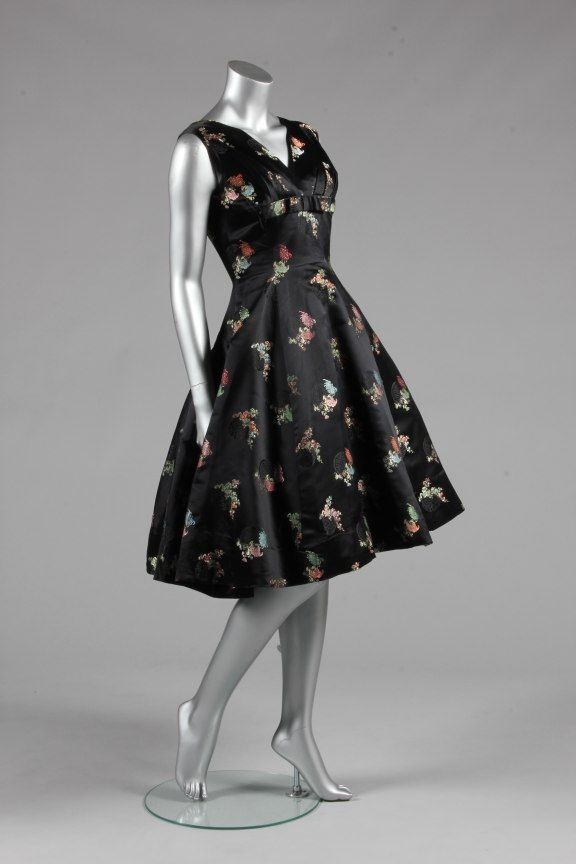 A Jacques Heim couture oriental brocaded satin dress, circa 1959, labelled, the black satin ground woven with pastel blossom and damask roundels, the fitted princess-line bodice with bow to breast and rear waist, bust 86cm, 34in, waist 66cm, 26in - See more at: http://kerrytaylorauctions.com/archive-list/?id=63&sts=archive&paging=4#sthash.p9qYFzZd.dpuf