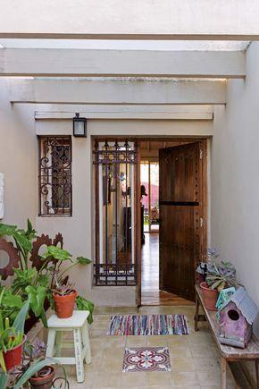 Patio de entrada en una casa con puerta y banco de madera, rejas en las ventanas, piso de cerámica y plantas en macetas.