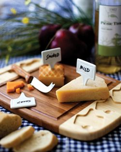 This Delio is a two-toned bamboo cutting board that has carved out grooves to hold a cheese knife and three ceramic cheese markers.