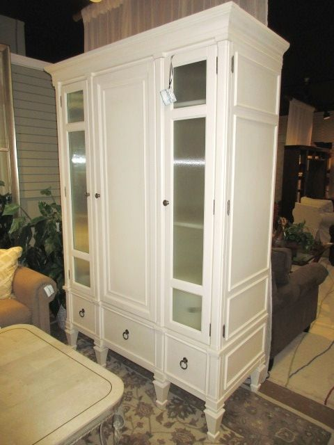 Transitional style armoire in cream with ribbed glass front doors. This armoire cabinet offers plenty of storage space with six drawer and three shelves. You could place a wardrobe bar inside. 57