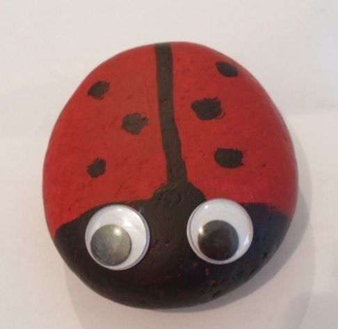 Stone painted as a ladybug.