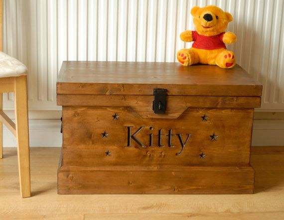 Designed and created in our Warwickshire studio is a handmade bespoke childrens toy box suitable for both girls and boys.  It is made from new carefully sourced seasoned pine and is handcrafted to be a sturdy, useful and long lasting piece of furniture. This box is made from new timber so it has no rot, woodworm, rusty nails or splinters.  This handmade toy box has been crafted to replicate the look of a vintage travel trunk.  The top of the box is flat to provide a useful surface and is…