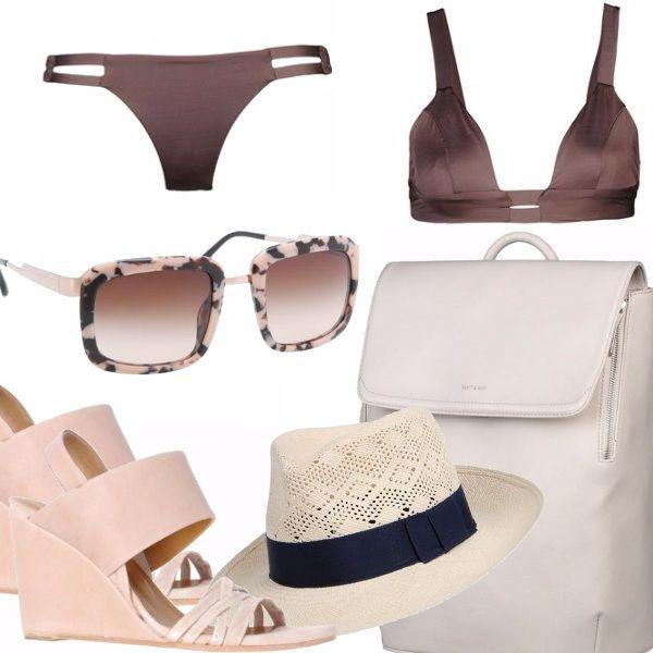 Bikini con reggiseno imbottito color marrone, sandali con zeppa, zainetto dalla linea pulita, occhiali da sole con montatura camouflage, fedora con nastro a contrasto.