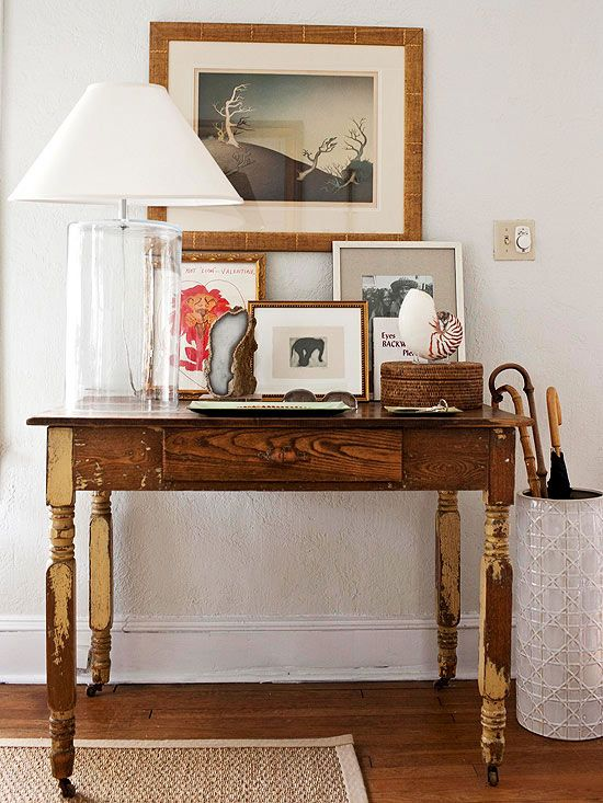 Look to images like this for display ideas. Note the art layering, the box on the table, the tray, the lighting, and even the umbrella stand. All great decor display ideas.