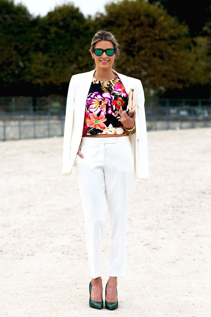 White cropped trousers, blazer draped over the shoulders, patterned top, and mirrored sunglasses