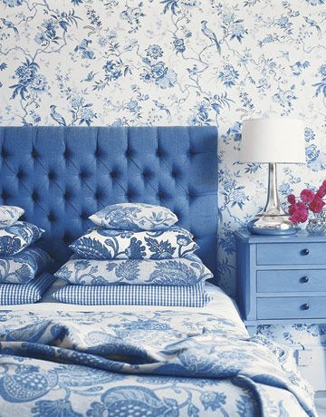 The solid blue headboard and furniture creates balance in the 'sea' of patterns.  A single hue for the entire room allows it to feel comfortable, not busy, despite all of the different patterns.