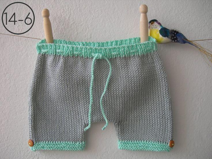 Pantalón en punto jersey de color gris con elásticos en color aguamarina. El elástico de la cintura lleva un cordón para ajustar y los de las piernas en punto bobo con botón de madera lateral.