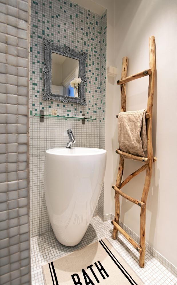 Både vegger og gulv på badet er dekket av hvite mosaikkfliser, mens det over vasken er blandet med turkise. En stige av greiner står lent mot veggen, og fungerer som håndkleholder.
