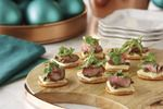 The combination of savory beef, slightly bitter arugula and salty capers really complements the bold flavor of white cheddar cheese on these crackers.