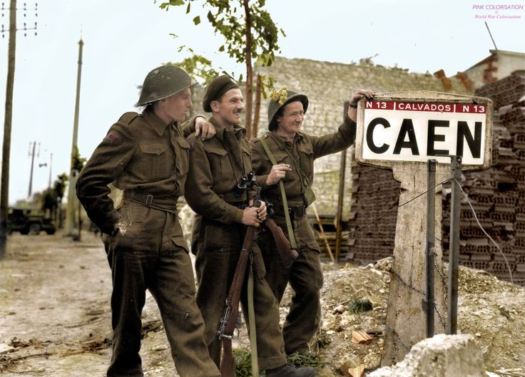 From left to right : Bernard Hoo, John Mc Couville, JR Kostick in are standing next to a sign Caen by the RN13. 10th July, 1944. - The three men survived the war and returned to the same place in 1974 and another photo was taken, this time with the Deputy Mayor of Caen.
