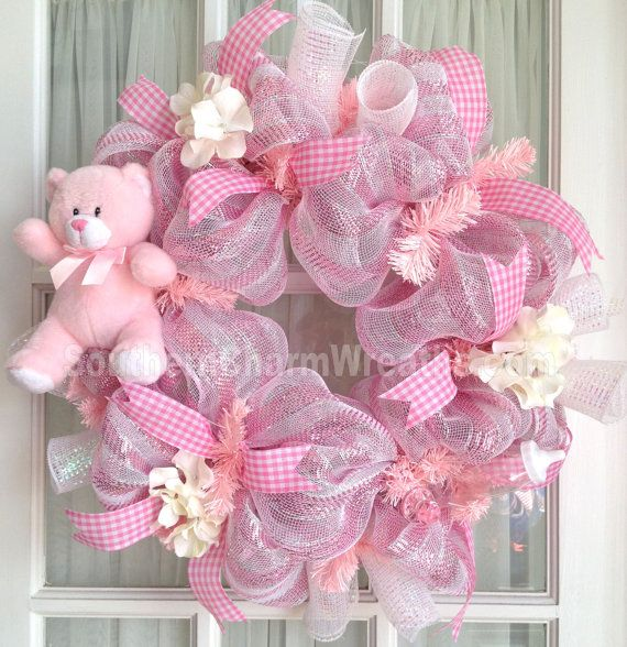 Display your joy of your new arrival with this precious handmade deco mesh baby girl wreath in pink and white with teddy bear. Great baby