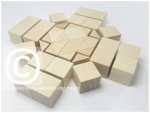 """Spielgabe 5 ist ein Sortiment mit Holzbausteinen. Designt vom Kindergartenerfinder Friedrich Fröbel. Es enthält Würfel und Dreiecks-Prismen. Wenn du diese Bausteine punktsymmetrisch im Kreis anordnest, entstehen Mandalas. Fröbel nannte diese Mandalas """"Schönheitsformen""""."""