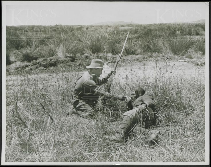 Photograph of an ANZAC soldier giving a drink to a wounded Turkish prisoner. No 2606. From a collection of official photographs of the Dardanelles Expedition, 1915-1916.