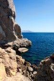 Viajes, vacaciones de fondo - vertical de roca, montaña, mar azul profundo y hermoso cielo stock photography