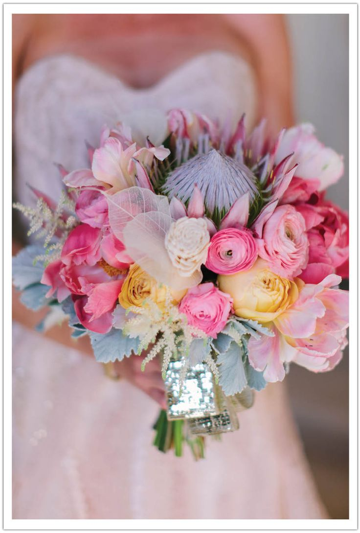 Arrangements Floral  Party Design crafted a stunning bouquet of coral charm peonies, king proteas, ranunculus, astilbe, tulips and a skeleton leaf.  Event design by Alchemy Fine Events   www.alchemyfineeevents.com