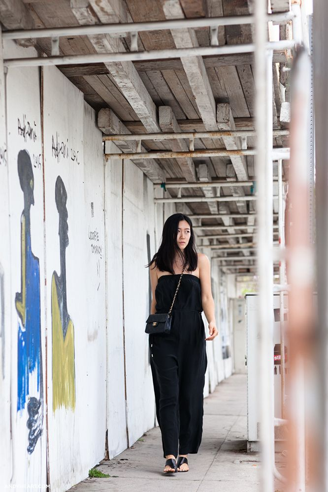 Andy Heart wears a black strapless jumpsuit, slide sandals, and a Chanel crossbody bag