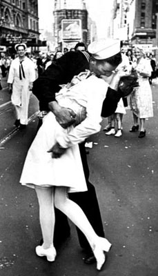 A jubilant American sailor clutches a white-uniformed nurse while thousands jam Times Square to celebrate the long awaited-victory over Japan.