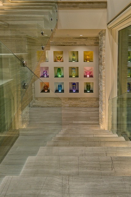 2012 International Builders' Show Home - Stone stairs with lighted steps  glass railing. Lighted display cubbies.