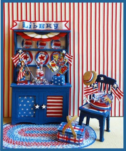 """1/4"""" Yankee Doodle - This 1/4"""" scale kit includes the hutch, chair, rug, picnic basket, Lady Liberty, straw hat, flags, firecrackers, and assorted accessories, artwork and instructions. Finished Size:  Hutch approx 1"""" w x 1 3/4"""" h. Chair approx 1/2"""" w x 1"""" h"""