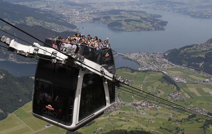 Pessoas acenam durante a travessia inaugural do primeiro vagão de teleférico de dois andares do mundo, batizado de 'Cabrio', na montanha de Stanserhorn, perto de Lucerne (Suíça). O andar de cima não tem teto. Ao fundo, o lago e a cidade de Lucerne.