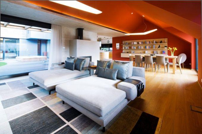 Na podlaze jsou použita dubová prkna, která jsou patrná také v pohledovém betonu na stěně a části stropu nad krbem. Klasickou sedací soupravu nahradila dvě denní lůžka Sherman (Minotti). Knihovna Pad (B & B Italia) s policemi zaplněnými knihami a zásuvky připevněné na stěnu vytvářejí efektní proměnlivý barevný obraz