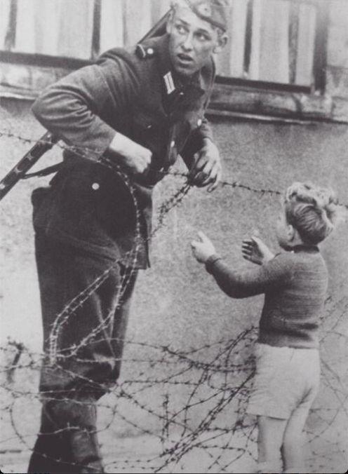 Soldado alemán del Este ayuda a un niño a cruzar el nuevo muro de Berlín para reunirse con su familia. 1961