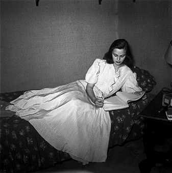The young Italian actress Lucia Bosè is reading a script very carefully, while lying on a bed. 1949. Getty image