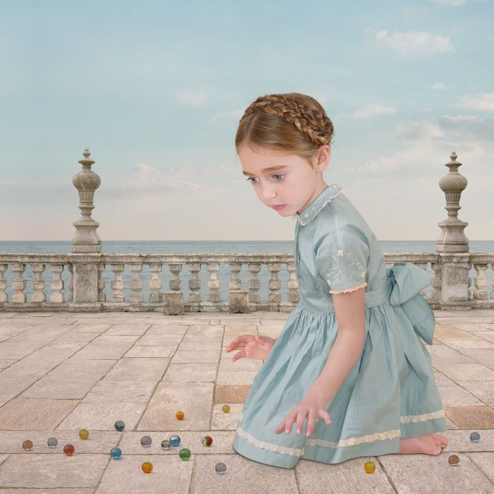 """""""Girl with Marbles"""" by Loretta Lux. This photo interested me with the unqiue background and overly large child, who seems to be staring at something that we cannot see in the photo."""