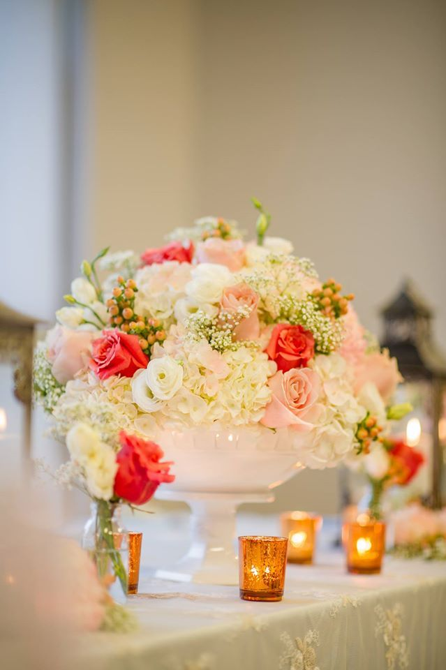 Coral and peach head table arrangement of mixed flowers