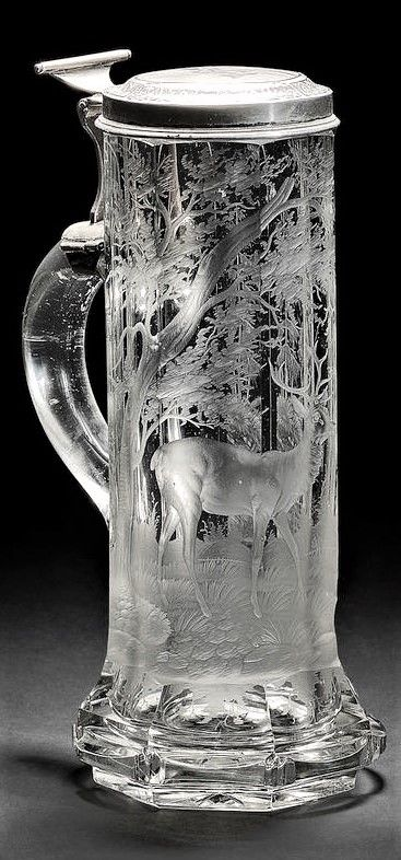 A Bohemian silver-mounted crystal glass tankard, the mounts dated 1874 In the manner of Johann F. Hoffmann, Carlsbad, cylindrical form cut with broad flutes and with a spreading foot, engraved with a stag standing in a forest, further deer beneath an overhanging rock in the distance, the hinged silver cover with niello decoration of a stag leaping a stream within a scrollwork border, presentation initials M W engraved on the interior of the lid, 21.2cm high