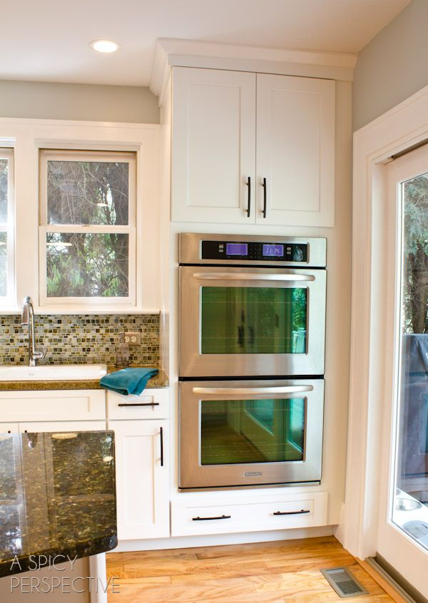 In wall doubleoven, white (more traditional) cabinets fridge anchors down other side of sink. Stove top in island.