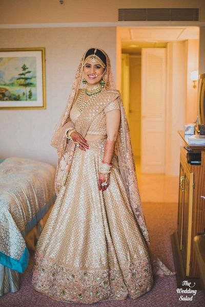 Sabyasachi bridal lehenga , gold bridal lehenga , polki and emerald necklaces, regal bride, mathapatti ,