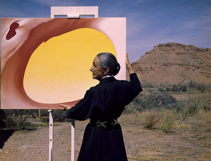 Photograph of artist Georgia O'Keeffe in the desert with one of her paintings.