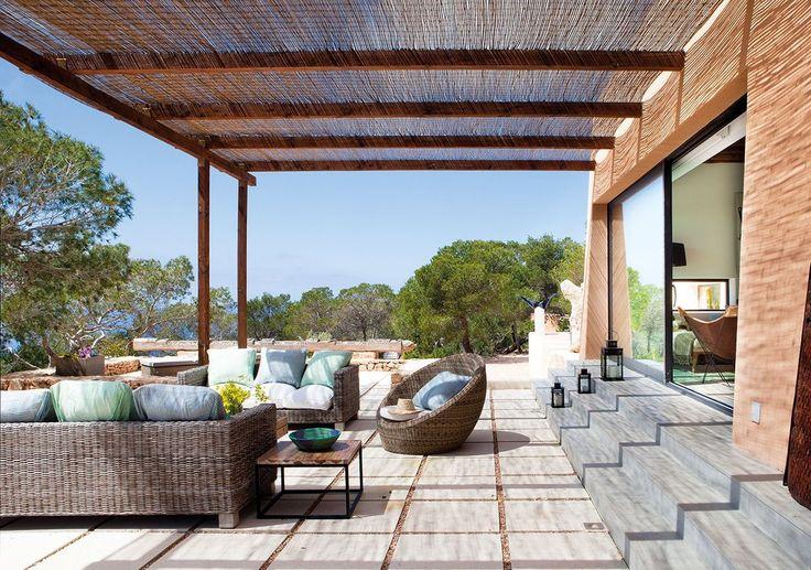 Своеобразная летняя гостиная на террасе под тростниковой крышей с плетеной мебелью.  (средиземноморский,архитектура,дизайн,экстерьер,интерьер,дизайн интерьера,мебель,на открытом воздухе,патио,балкон,терраса) .