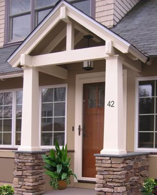 A crisp white trim, portico, and stone veneer at the base of the columns creates a cohesive and inviting entrance.