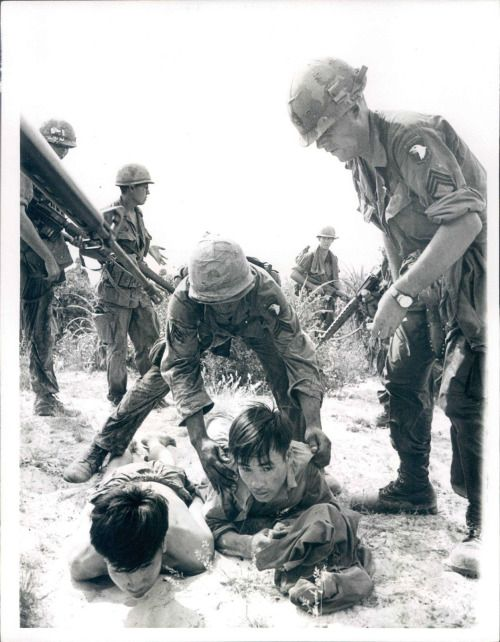 Members of the 101st Air Calvary search two captured North Vietnamese soldiers near the battered old imperial capital of Hue July 21st. U.S. Calvarymen killed 11 Communist soldiers in sharp fighting near Hue July 25th. A military spokesman said other patroling American troops trying to prevent a new attack on the city uncovered a huge weapon cache. UIP PHOTO 7/26/68