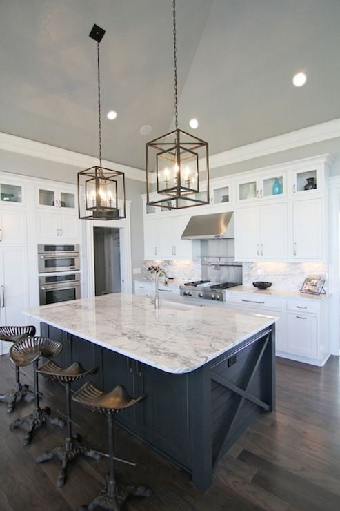 White and navy kitchen features iron and glass cage lanterns over navy center island accented with x trim moldings topped with white and gray stone countertops lined with Restoration Hardware Tractor Seat Barstools atop dark floors. A row of small glass-front cabinets are stacked over white shaker cabinets paired with white and grey stone countertops and matching backsplash. A stainless steel hood over swing-arm pot filler on stainless steel back splash above integrated gas range.