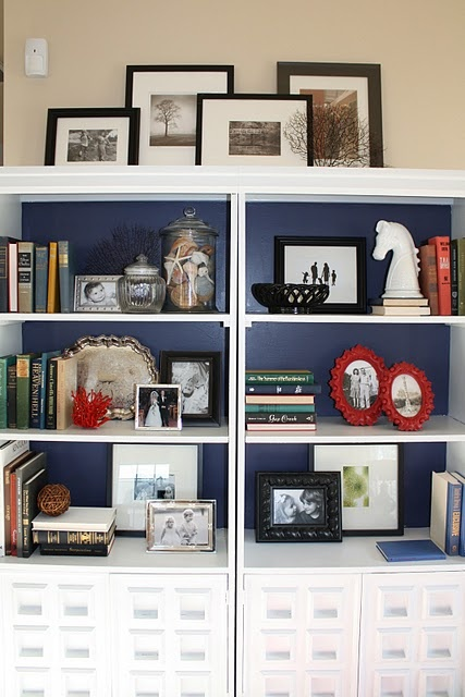 Bookcase in Emily Clark's family room -- love the detailing and navy background making the white pop. ~~~`