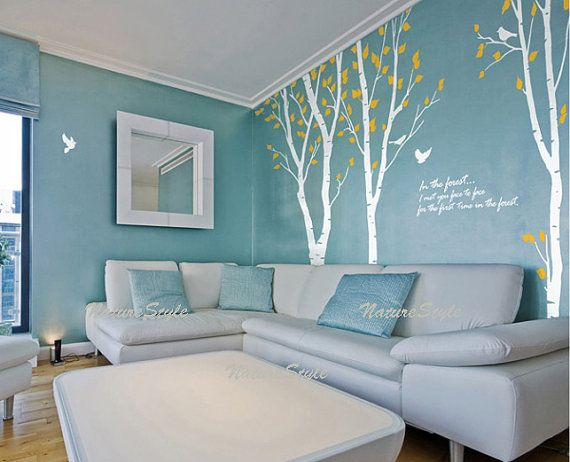 Adding tree decals to a pretty duck egg blue living room adds a whimsical quality to the decor.