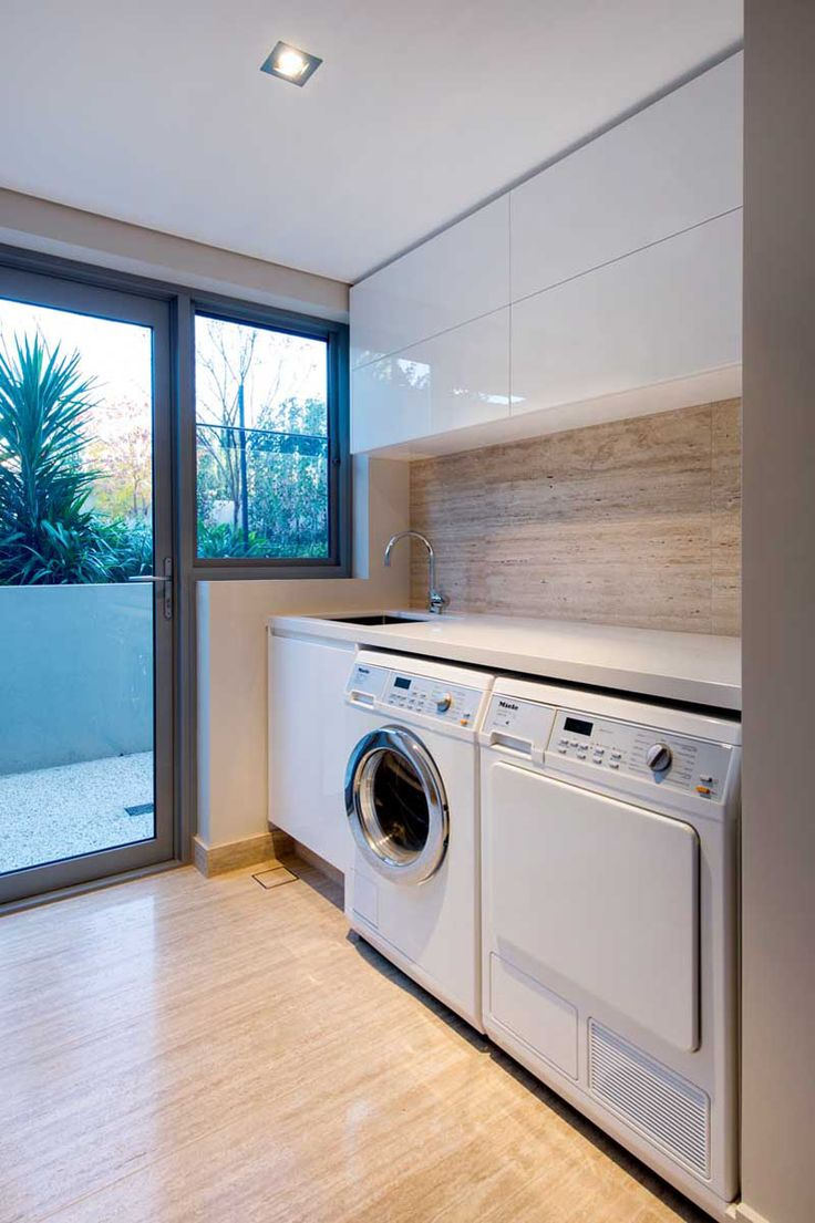9 Inspirational Laundry Rooms You Need In Your Life // This laundry room has access to the outdoors, and includes as much storage as possible, but also leaves room for a nice counter for folding clothes.