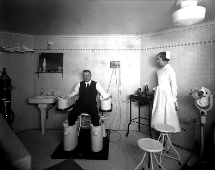 """A Nurse Ratchet looks on as a patient experiences a """"Schnee Bath"""" in the Chateau Laurier Therapeutic Department, 1931."""