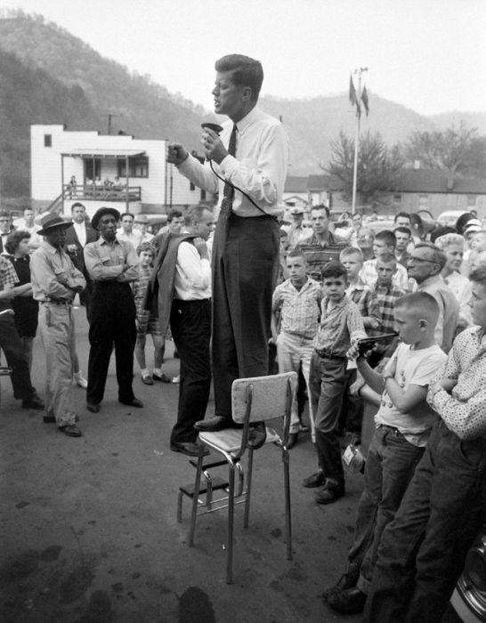 John F. Kennedy dando un discurso de campaña en Logan County, West Virginia, parado en una silla de cocina: