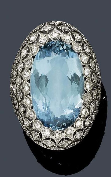 AN ART DECO AQUAMARINE AND DIAMOND RING, ca. 1920. Oval domed ring finely pierced in openwork palmette patterns, set with single-cut diamonds, and centring one aquamarine weighing 9.5 carats, mounted in platinum.