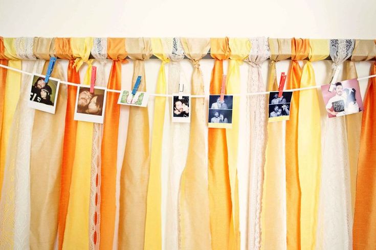 Strips of colorful fabric tied on a bar + pictures. Good idea for weddings and looks cute as a headboard in a bedroom